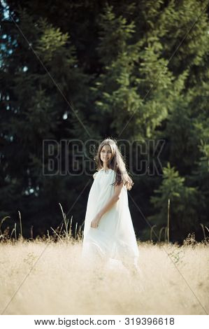Beautiful Girl Laughs And Dances Outdoors In Meadow During Sunset