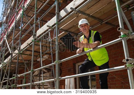 Male builder foreman, construction worker, surveyor or architect on site holding a clipboard and drinking a mug of coffee or tea