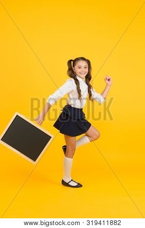 Getting Back In Study Mode. Energetic Little Girl Going To School On Yellow Background. Small Child