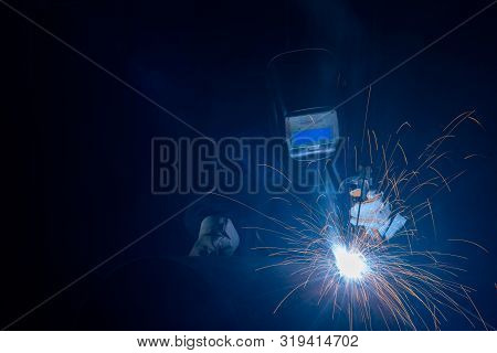 Professional Welder And Mask Welding Metal Pipe On The Industrial Table.a Welder Is A Tradesperson W