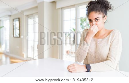 Beautiful young african american woman with afro hair sitting on table at home smelling something stinky and disgusting, intolerable smell, holding breath with fingers on nose. Bad smells concept.
