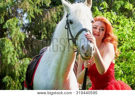 Portrait Of A Beautiful Girl With Red Hair In A Red Dressy Dress Near With A White Horse On A Green