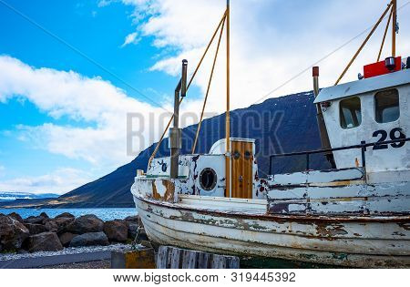 Isafjordur, Iceland - June 1, 2019: A Ruined Fishermen Boat On The Seafront