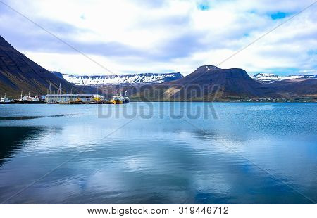 Isafjordur, Iceland, View Of The Bay With The Fishermen Harbor And The Mountains With Snow In The Ba