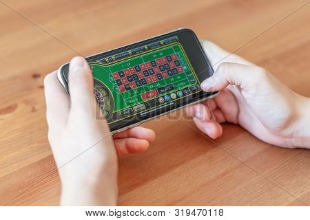 London / Uk, August 24th 2019 - Closeup Of Hands Gambling On Mobile Phone Device, With A Shallow Dep