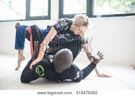 Woman And Man Doing Bjj Brazilian Jiu-jitsu Ground Fighting Training
