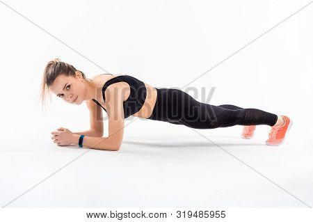 Young Sporty Blond Woman In A Black Sportswear Holding Plank Position Exercising Isolated Over White
