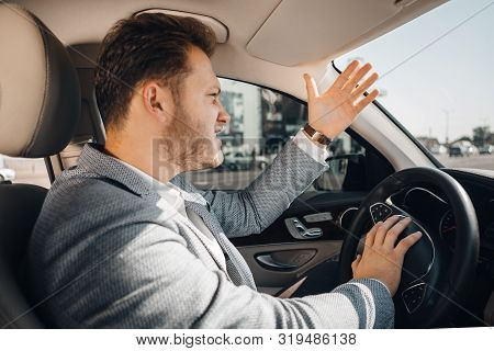 Angry Driver In A Traffic Jam Loosing His Tamper And Gesturing To Let His Car Go. Being Late