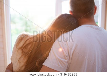 A couple in love embracing. Girlfriend and boyfriend standing home by the window