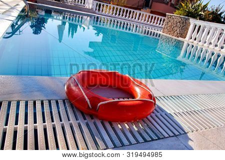 Red Lifebuoy Pool Ring At Swimming Pool. Red Pool Ring In Cool Blue Refreshing Blue Pool, Room For Y