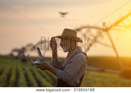 Old Farmer With Hat Holding Remote Control For Drone Flying Above Soybean Field With Irrigation Syst