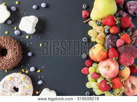 A Lot Of Natural And Healthy Vitamin Fruits, Berries Vs Sweet And Junk Food On A Black Background. V