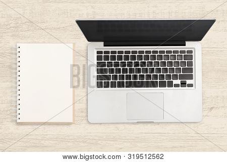 Laptop Computer And Blank Notebook On Wooden Table.