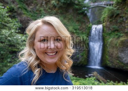 Happy Blond Woman (30-35 Years Old) Poses At Multnomah Falls In Oregon