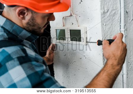 selective focus of bearded workman repairing control panel with screwdriver poster