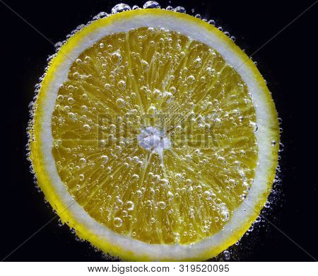 A Slice Of Fresh Juicy Orange Under Water Is Covered With Small Air Bubbles