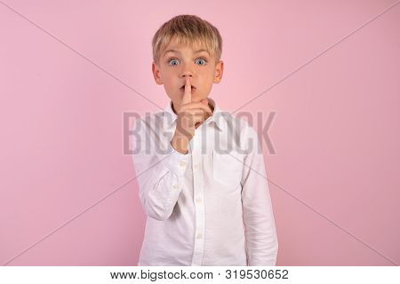 Serious Good Looking Young Boy With Trendy Hairdo, Keep Fore Finger On Lips, Tries To Keep Conspirac