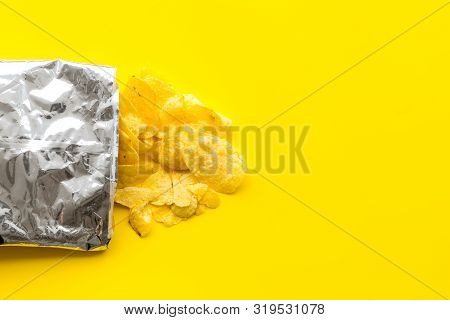 Bag Of Homemade Potato Chips For Snack On Yellow Background Top View Copyspace