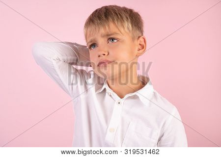 Photo Of Puzzled Boy With Stubble, Scratches Head, Looks In Bewilderment, Dressed In Casual White Sh