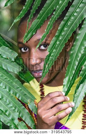 Face Of African Woman Hid Behind Green Leaves