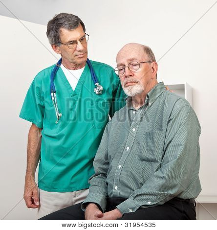 Male Doctor Or Nurse Listening To Depressed Senior Patient's Problems