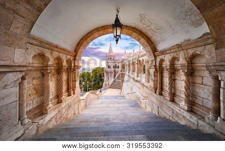 Budapest, Hungary. Ancient Fishermans Bastion castle. View at tower from stairs under arch along gallery with columns and street lantern. Picturesque evening sunset with clouds on sky. Famous.