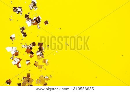 Falling Silver Confetti On Yellow Backdrop. Holiday Concept.