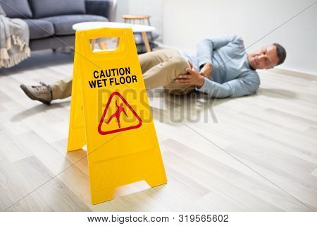 Mature Man Falling On Wet Floor In Front Of Caution Sign At Home