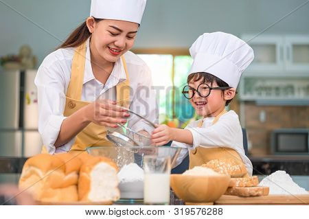 Cute Little Asian Boy And Beautiful Mother Sifting Dough Flour With Sifter Sieve Colander In Home Ki