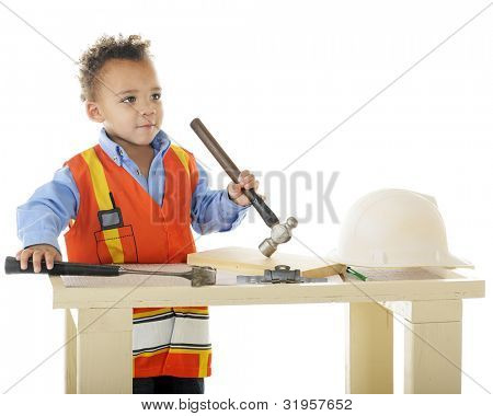"A biracial preschool ""construction worker"" standing at his workbench holding two hammers.  On a white background."