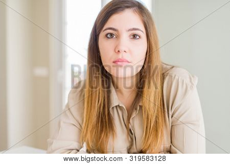 Beautiful young woman at home with serious expression on face. Simple and natural looking at the camera.