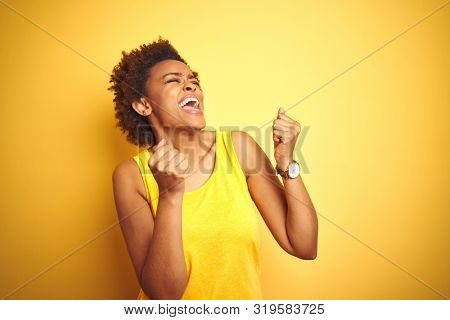 Beauitul african american woman wearing summer t-shirt over isolated yellow background very happy and excited doing winner gesture with arms raised, smiling and screaming for success.