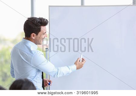 Caucasian Businessman Coaching In Team Meeting Or Training, Speaker Drawing Something On Blank White