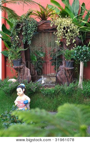 Clay Doll And Waterfall In The Garden.