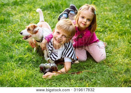 Kids Play With Cute Jack Russel Terrier. Children And Dog Playing In Sunny Summer Garden. Little Gir