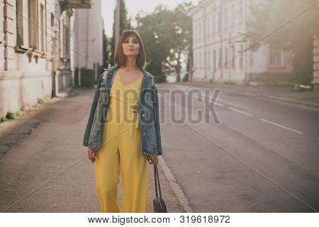 Young Beautiful Fashion Woman Wearing Stylish Yellow Jumpsuit Posing On European City Streets.