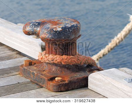 Weathered Mooring Bollard With Ships Rope At A Jetty