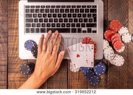 Online Betting Or Poker. Top View Of A Computer With Chips And Cards For Betting Or Playing. Online