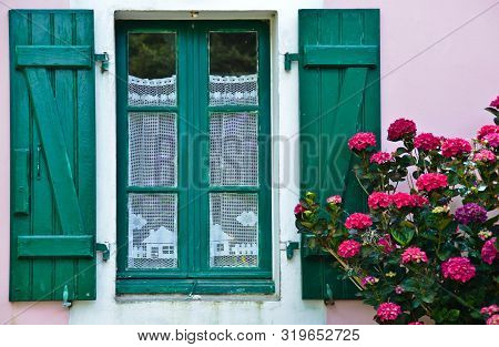 Sunny View Of A Green Window Of An Old Farm House With Shutters, Where A Curtain Of Handmade Crochet