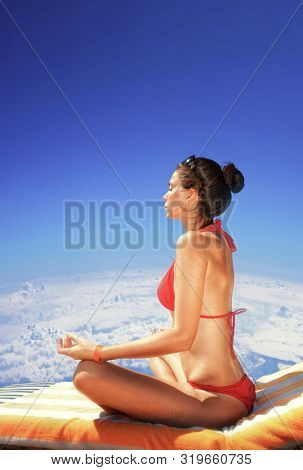 girl sitting in lotus position against a blue sky