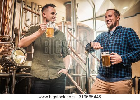 Two men tasting fresh beer in a brewery