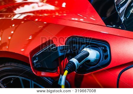 Red Ev Car At Charging Station With The Power Cable Supply Plugged In. Power Supply Connect To Elect