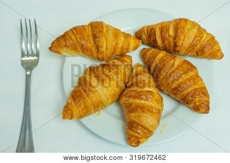 Puffy golden croissant on white plate on white background poster