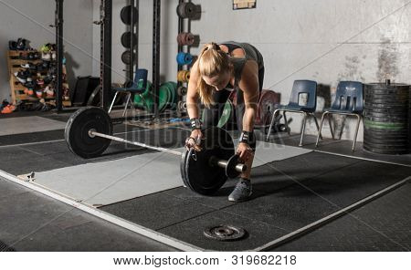 Strong young female weight lifter loading weights onto barbell in gym.