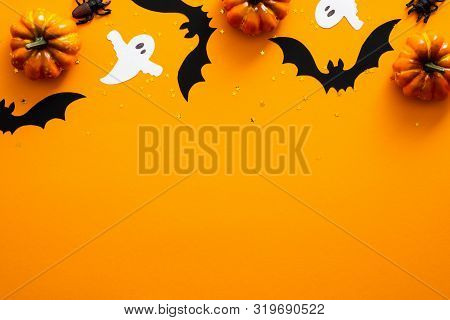 Happy Halloween Holiday Concept. Halloween Decorations, Pumpkins, Bats, Ghosts On Orange Background.