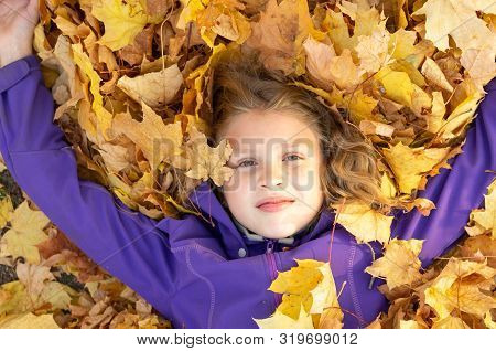 The Girl Is Wallowing In The Yellow Foliage. Girl Is Enjoying Autumn. Close Up.