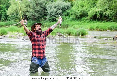 Fish On Hook. Brutal Man Wear Rubber Boots Stand In River Water. Satisfied Fisher. Fisher Masculine