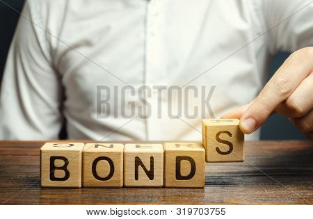Businessman Puts Wooden Blocks With The Word Bonds. A Bond Is A Security That Indicates That The Inv