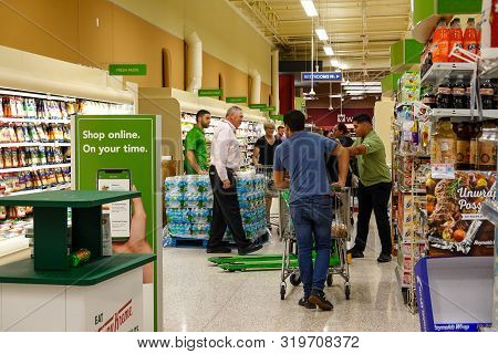 Orlando,fl/usa-8/30/19: Grocery Store Employees Handing Out Rationed Bottles Of Water.