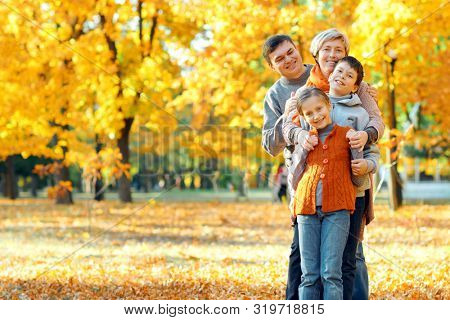Happy family posing, playing and having fun in autumn city park. Children and parents together having a nice day. Bright sunlight and yellow leaves on trees, fall season.